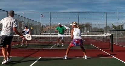 4 people playing pickleball on a sunny day